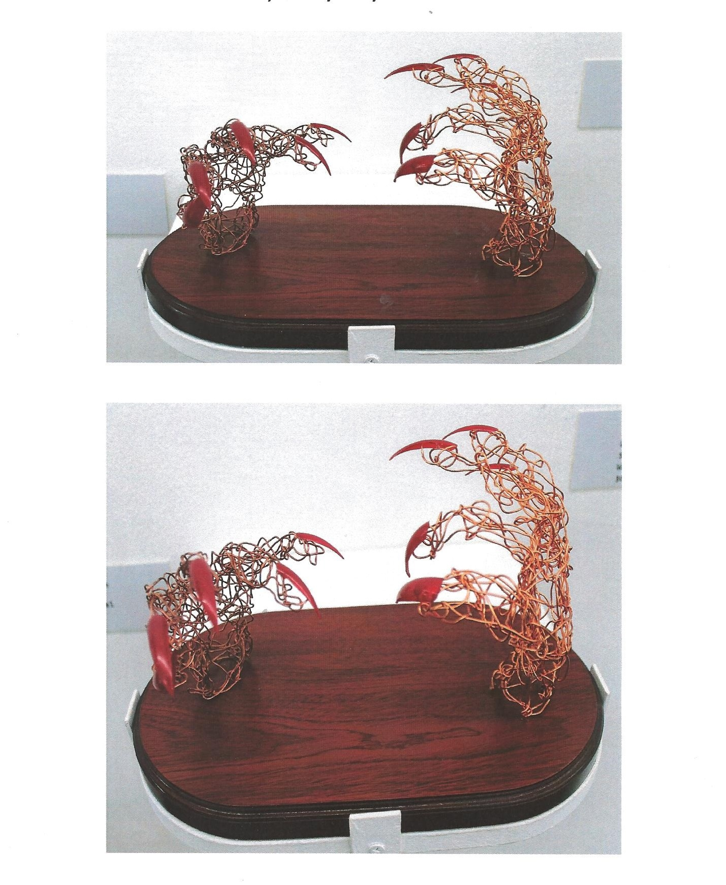 images of wire hands sculpture with red talons on wooden plinth