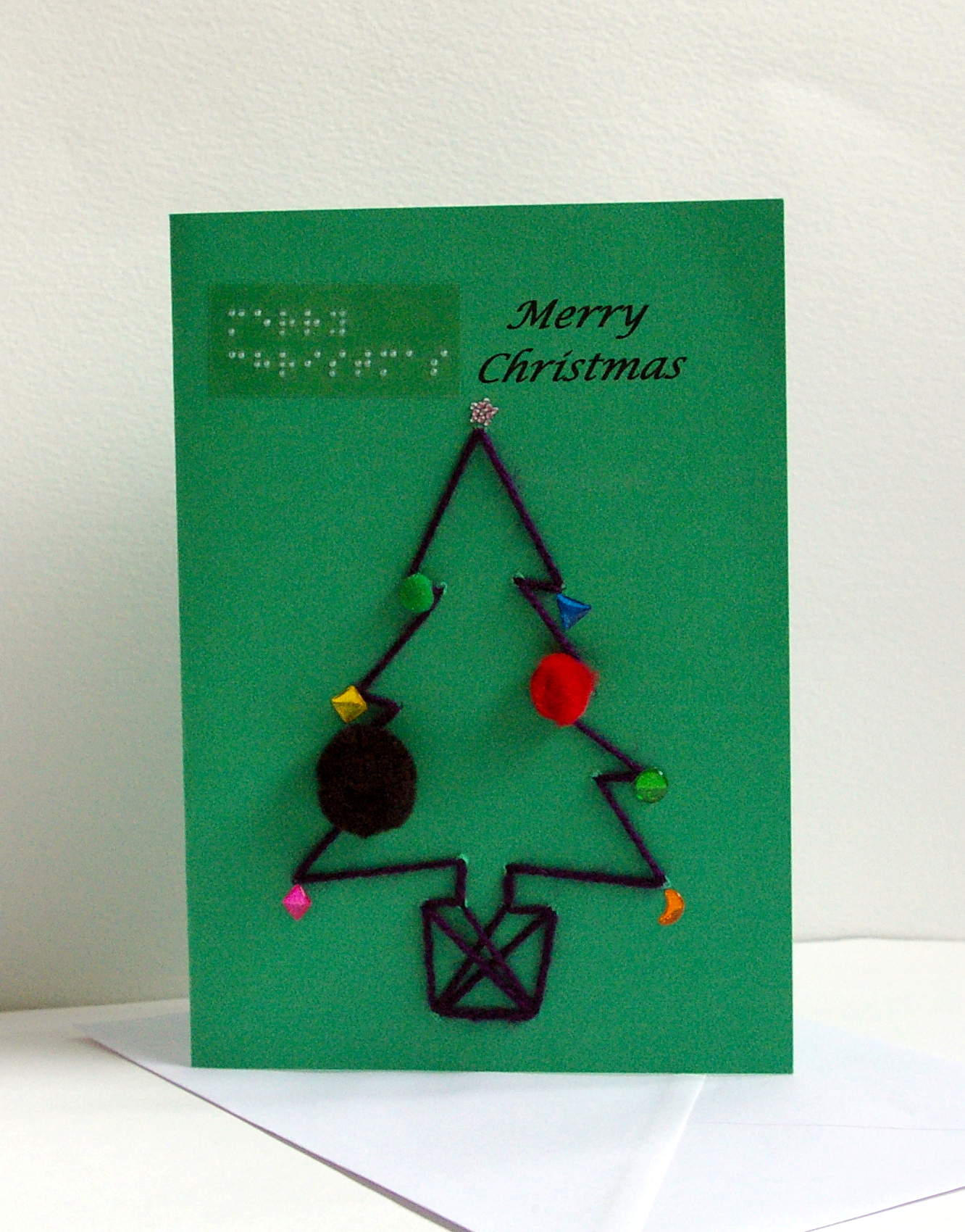 dark wool christmas tree in pot with pom pom and gem sticker decorations merry Christmas card