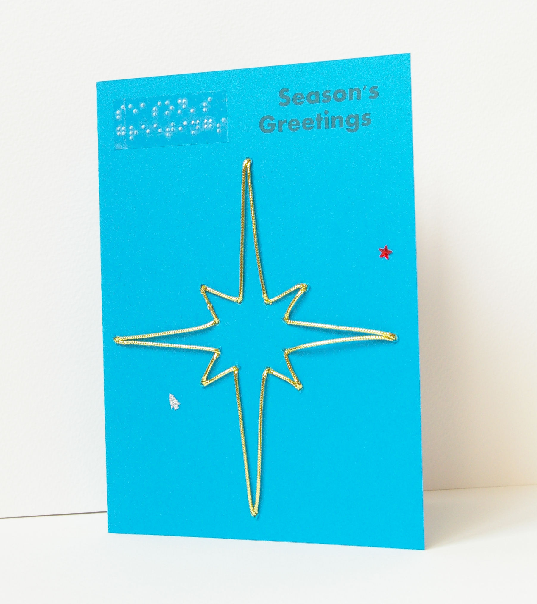 Gold sparkly star season's greetings card on blue card