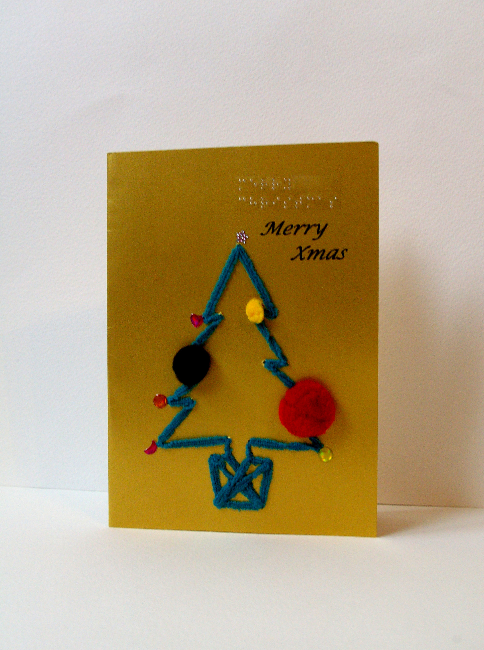 fluffy green Christmas tree in pot with pom pom decorations on gold card