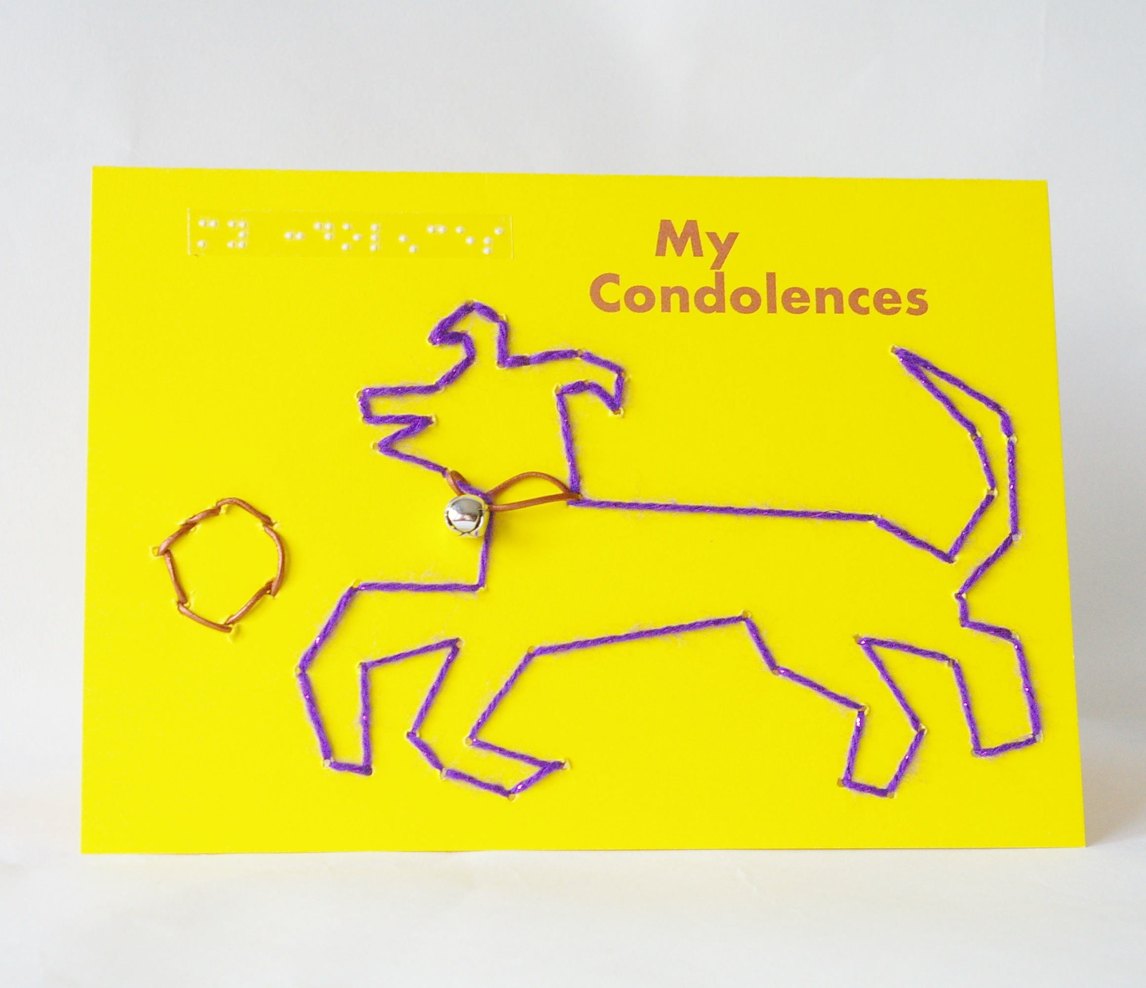 Purple sparkly dog with leather collar and silver bell audible, playing with leather ball on landscape yellow card